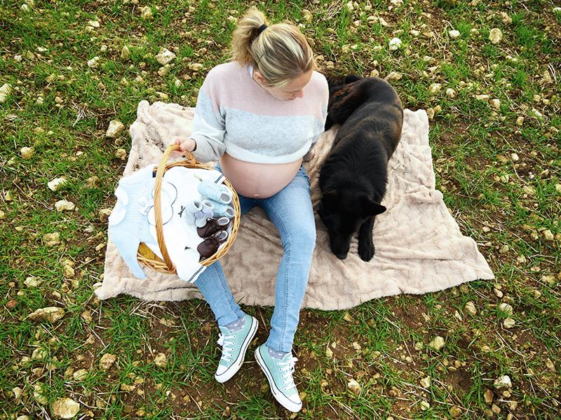 Femme enceinte assise dans l'herbe avec son chien à ses côtés
