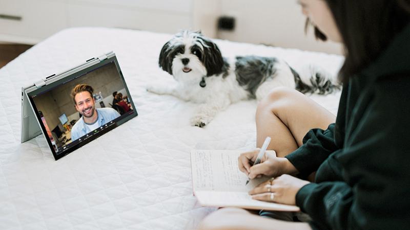Femme prenant des notes lors d'une consultation en télémédecine avec son chien à côté